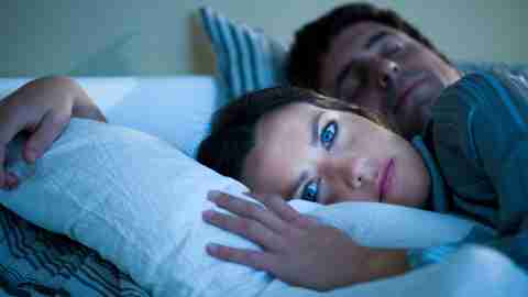 A woman can't sleep beside her husband sleeping soundly.
