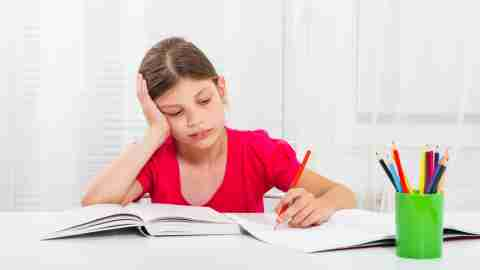 A girl looks glum while she writes an essay about the different types of learning disabilities.
