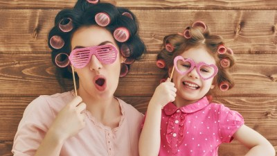 A parent and child with ADHD have fun with hair curlers and sunglasses