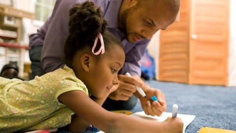 Father helping his child, who has ADHD, complete her homework