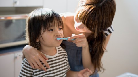 A mother helps her child, who has ADHD, brush her teeth