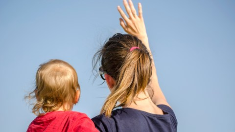 A woman holding a child waves goodbye to ineffective ADHD therapy.