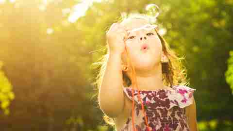 A little girl with ADHD blows bubbles.