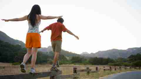 Two people with ADHD balance on a fence.