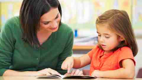 A teacher works with a child who has autism spectrum disorder.
