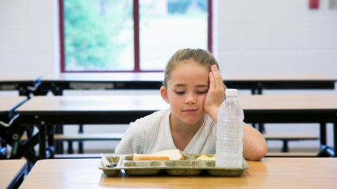 Socially rejected by her peers, a sad girl eats lunch alone.