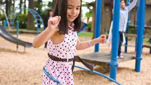 A girl is hula-hooping on the playground, but ostracized for being hyperactive.