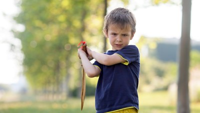 A defiant boy with Oppositional Defiant Disorder (ODD) and ADHD plays with a toy sword.