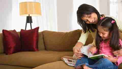 A mom practices positive parenting by reading with her daughter with ADHD.