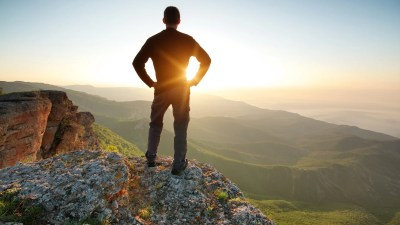 A man at the top of a mountain, no longer feeling overwhelmed by life