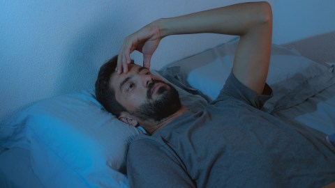 A man with ADHD lays in bed awake with insomnia