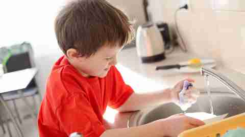 A child with ADHD does dishes as discipline for misbehaving.