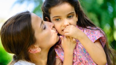 A mom kisses her daughter with ADHD on the cheek.