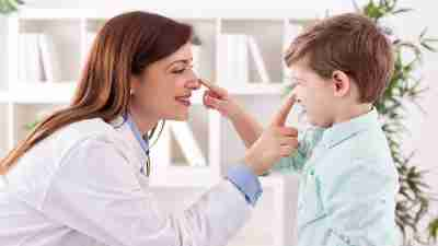 A doctor talks to a little boy patient while his parent ask about a drug holiday on his ADHD medications.
