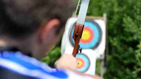 Boy with ADHD doing archery at accredited ADHD camp