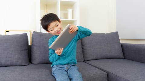 Boy playing on a tablet, reveling in the freedom of his summer schedule
