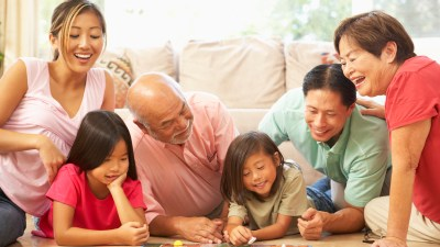 A family playing a board game together during the summer to avoid learning loss