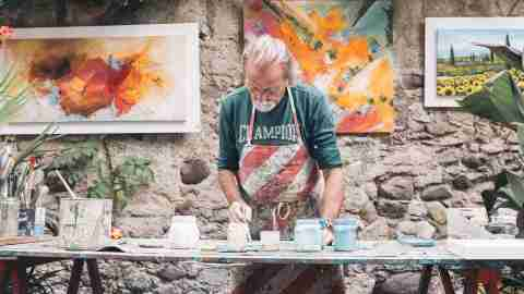 Artist with ADHD, surrounded by materials and artwork behind him, painting and selling work outside