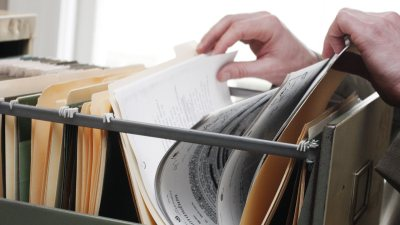 Hands of person with ADHD searching through bills in file cabinet