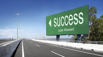 "Empy highway road with large sign saying ""success just ahead"" signifying a possible path for people with ADHD"