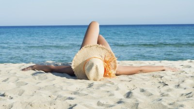 A woman laying on a beautiful beach, a common ADHD relaxation technique