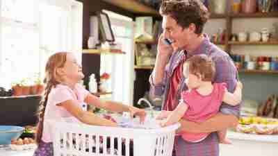 Father with ADHD holds baby while on cellphone and smiling at other child while sorting laundry