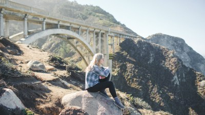 An adult woman with inattentive ADHD, sitting near a bridge and looking at the landscape