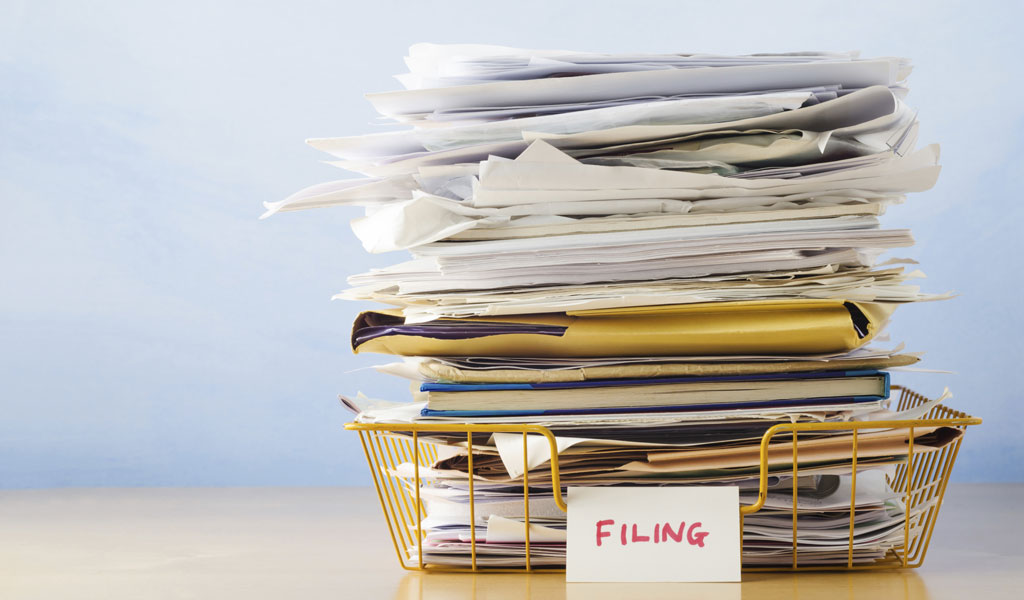 Filing bin on table filled with paperwork belonging to ADHD Adult