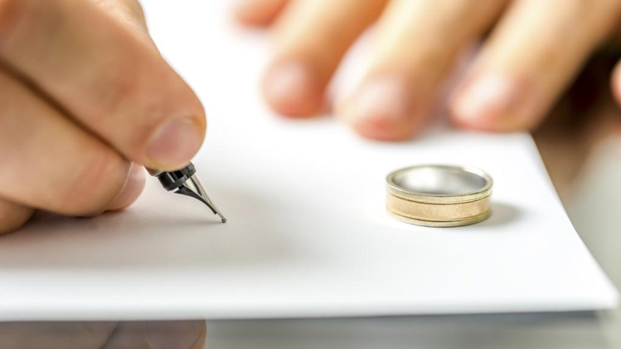Close up of hand of person with ADHD signing divorce papers with ring near by