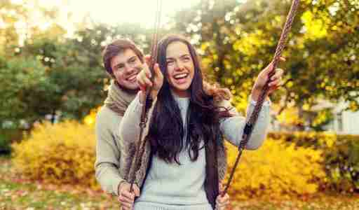 Married man with ADHD pushing his wife on swing outside in autumn