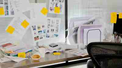 An ADHD adult's messy desk with papers, post-its, and cups