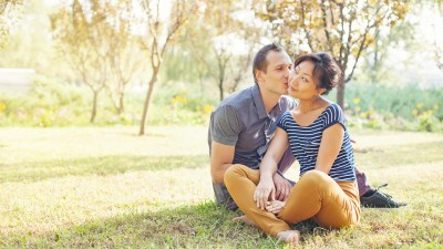 A happy couple sitting on the grass, sharing funny stories of their ADHD marriage.