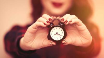 Woman with ADHD holding a small clock