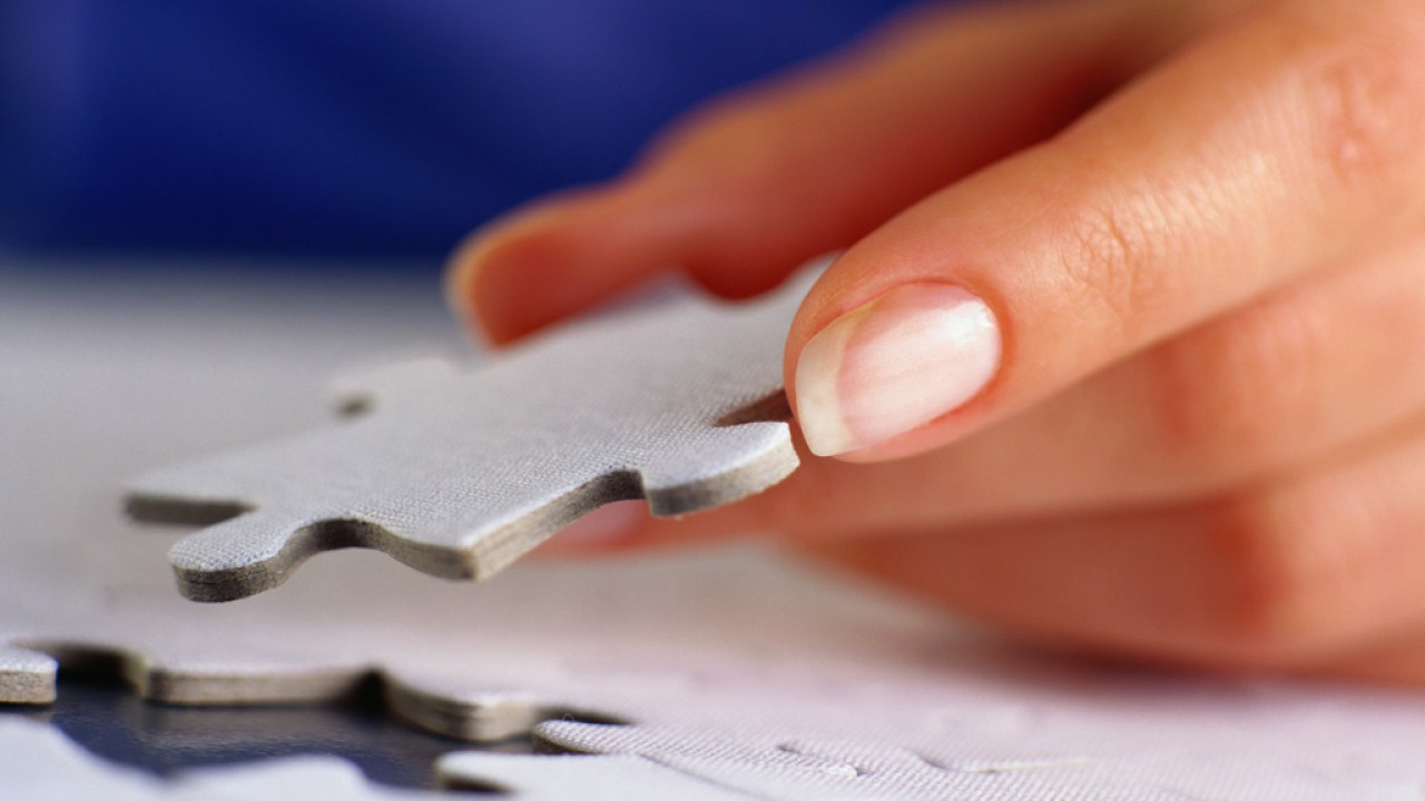 Hand of person with ADHD or a learning disability holding puzzle piece in hand while completing puzzle