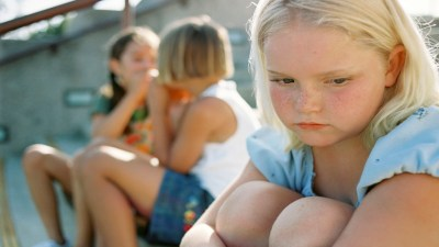 Girl with ADHD hugging knees and looking upset because two girls are bullying her.