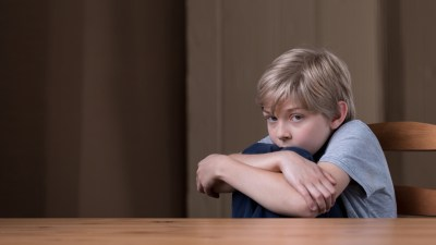 A young boy with ADHD, experiencing sensory overload and hugging his knees