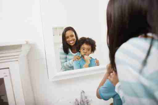 Mother encourages son with ADHD and sensory issues as he brushes his teeth with a sensitive toothbrush