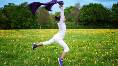 Girl with ADHD jumping in field outside