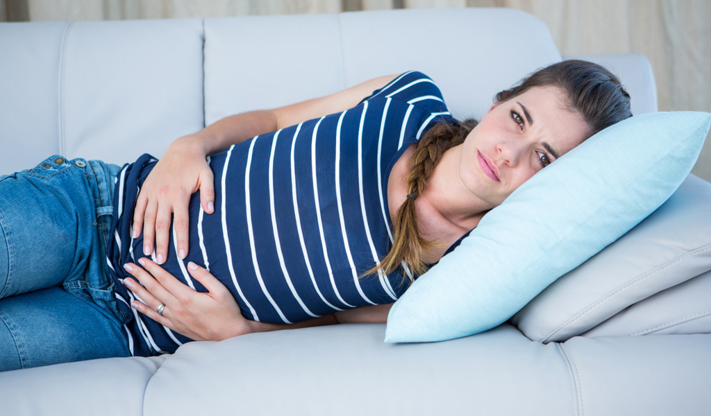 Woman with ADHD laying on couch, holding stomach and suffering from mentrual cramps