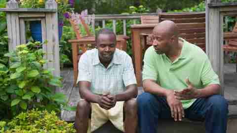 Two men speaking about ADHD on backyard porch