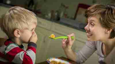 Mother enthusiastically spoonfeeding misbehaving ADHD son who has his hand over his mouth