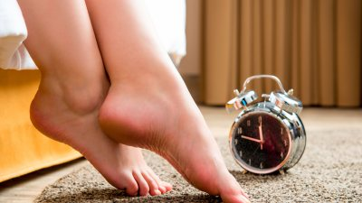 Feet of woman with ADHD hang off bed in the morning next to alarm clock signaling start of routine