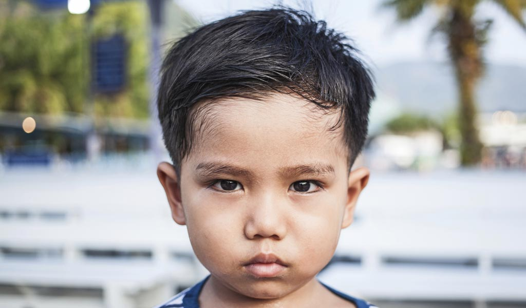 Sad little boy with ADHD frowning into camera