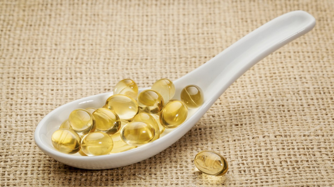 Spoon filled with fish oil capsules on burlap tablecloth, a good source of Omega 3 for people with ADHD