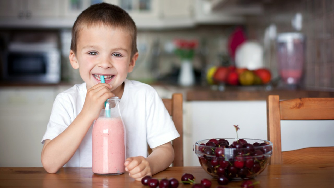 Boy with ADHD smiling while drinking smoothie from straw at table in kitchen