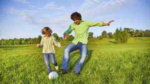 Father and son with ADHD playing soccor outside in field