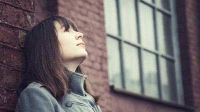 Girl with ADHD leaning against brick wall and staring at sky thinking about her friends