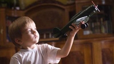 Boy with ADHD in living room playing with model airplane