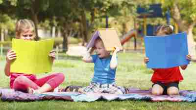 Three kids with ADHD reading books in the summer