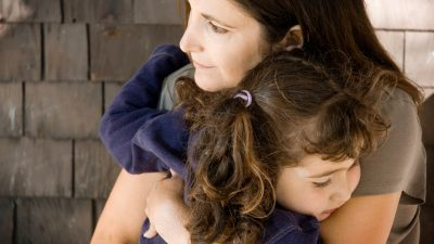 A parent giving an ADHD child a well timed hug to help her bounce back from a failure.